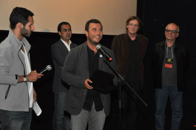 """Nikos Dayandas, diretor do filme """"Pedacinho de Terra"""", recebe o Prêmio """"Menção Especial"""" do júri de Longa Metragem (da esq. p/ dir.: Mário Branquinho, Chris Paine e Artur Xexéo)"""