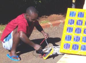 A trainee technician uses a multimeter to measure the output of a solar panel he has made. Photo: B. Cameron