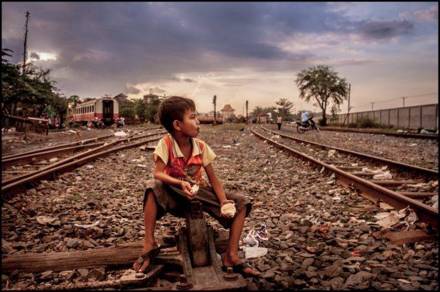 Menino em linha de trem próximo a favela no Camboja. Foto Zoriah CC